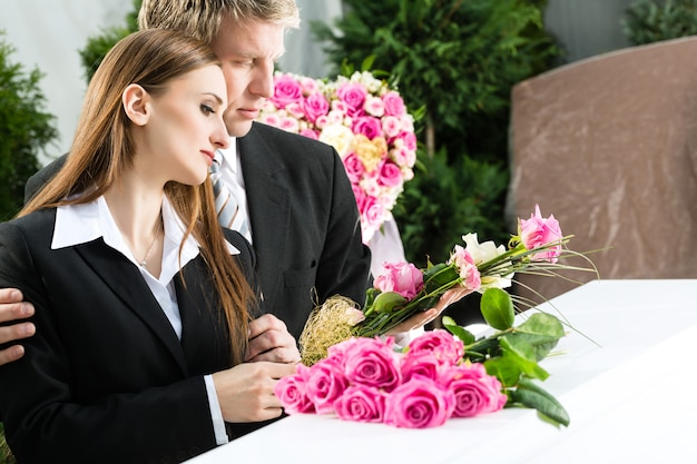 Persone in lutto al funerale con la bara