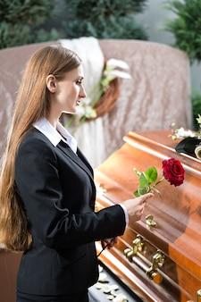 Donna funebre al funerale con la bara