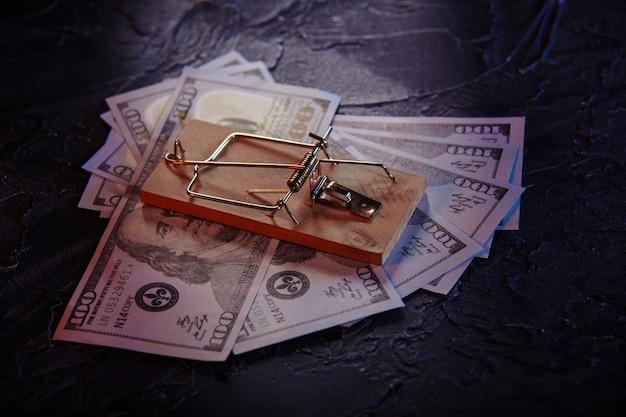 Trappola per topi con esca libera e banconote da un dollaro su uno sfondo grigio. trap, concetto di truffa di denaro