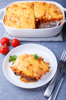 Moussaka con carne, melanzane, pomodori, patate, salsa bãƒâƒã'â©chamel e formaggio su un piatto bianco. piatto tradizionale greco. avvicinamento.