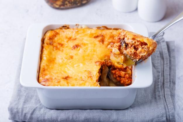 Moussaka con carne, melanzane, pomodori, patate, besciamella e formaggio su un piatto bianco. piatto tradizionale greco. avvicinamento.