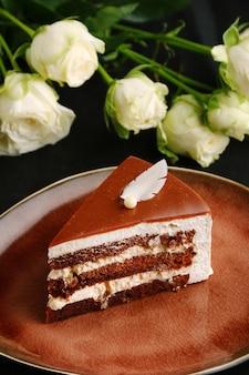 Primo piano della torta della mousse sulla zolla e sulla rosa