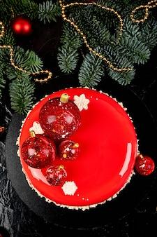 Mousse torta di natale pasticceria dolce ricoperta di glassa a specchio rosso con decorazioni di capodanno su lampade ghirlanda bokeh sfondo scuro, torta europea moderna tema natalizio.