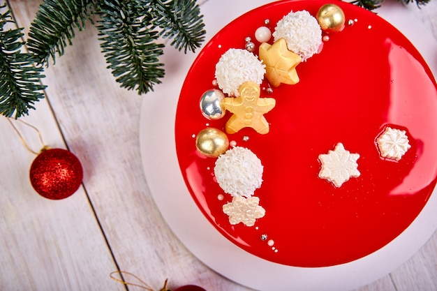 Mousse torta di natale pasticceria dolce ricoperto di glassa a specchio rosso con decorazioni di capodanno su lampade ghirlanda bokeh sfondo bianco, torta europea moderna tema natalizio.