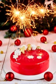 Dessert della torta della pasticceria di natale della mousse ricoperta di glassa rossa dello specchio con le decorazioni del nuovo anno sulla superficie bianca del bokeh delle stelle filanti, tema di natale della torta europea moderna.