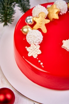 Mousse dolce di pasticceria natalizia ricoperta di glassa rossa a specchio