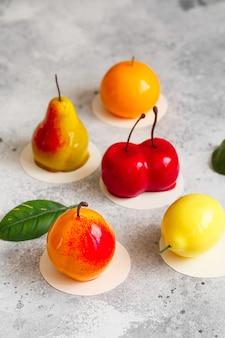 Mousse dolce a forma di pera, frutta arancia, albicocca, limone e ciliegia.
