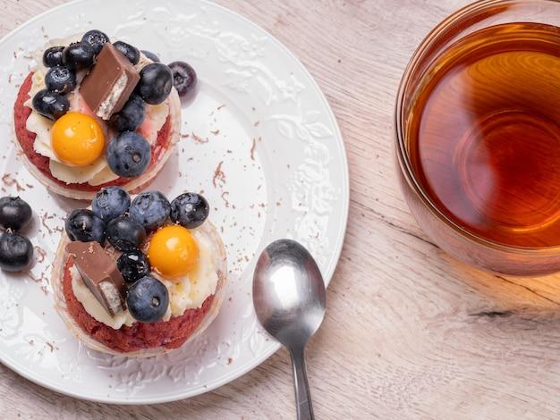 Muffin appetitosi con frutti di bosco e cioccolato e tè in una tazza rotonda di vetro su un tavolo di legno. colazione fatta in casa.