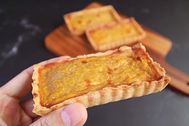 Tartelletta di zucca appetitosa in mano con tortine sfocate su tagliere di legno