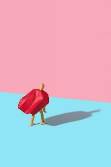 Modello in miniatura umano mobile in mantello rosso come un supereroe o un superuomo è in piedi