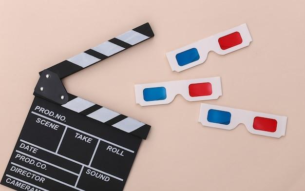 Ciak di film e occhiali 3d su sfondo beige. industria cinematografica, spettacolo. vista dall'alto