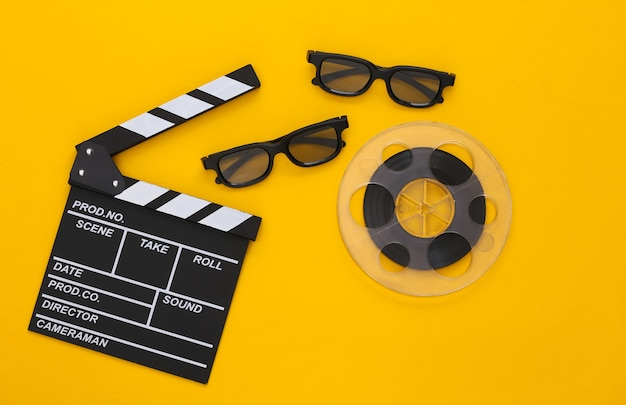 Batacchio di film, bobina di film e occhiali 3d su giallo. industria dell'intrattenimento. cinema