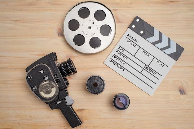 Batacchio di film, bobina di film e macchina fotografica su fondo di legno, vista dall'alto