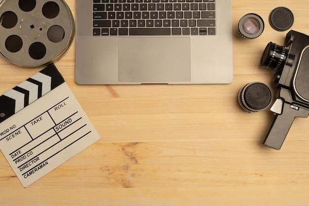 Batacchio di film, laptop e fotocamera su tavolo di legno, vista dall'alto