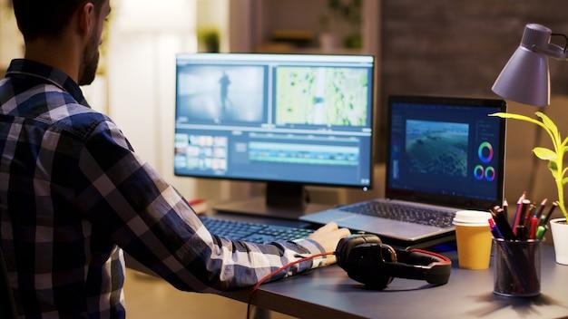 Creatore di film che modifica un film utilizzando un software moderno per la post produzione. giovane videomaker. ufficio a casa.