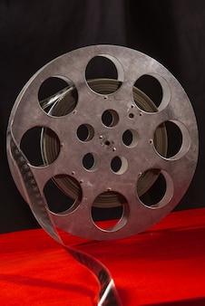 Bobina di film su un tavolo rosso e una superficie nera
