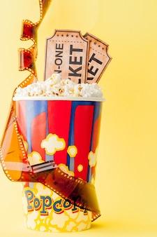 Biglietti per il cinema, strisce di pellicola e popcorn su sfondo blu. copia spazio per il testo.