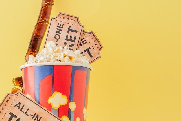 Biglietti per il cinema, strisce di pellicola e popcorn su giallo