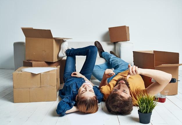 Trasferendosi in un appartamento un uomo e una donna giacciono sul pavimento e un fiore in un vaso.