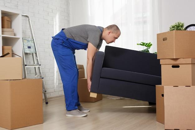 Concetto commovente - divano di sollevamento del caricatore dell'uomo in appartamento