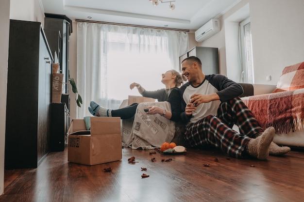 Celebrazione del giorno del trasloco giovane coppia si trasferisce in una nuova casa giovane coppia felice sposini famiglia che beve
