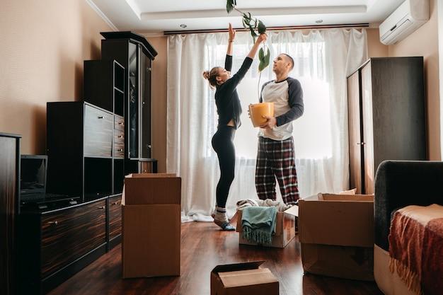 Il giorno del trasloco si trasferisce nella nuova casa giovane coppia felice famiglia di sposini che si diverte in camera con la pianta d'appartamento