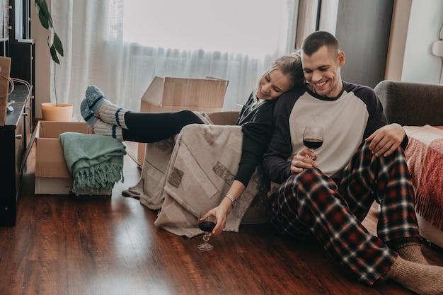 Giorno del trasloco, nuova casa, san valentino, disimballaggio delle scatole, concetto di sposini. coppia festeggia il trasferimento in una nuova casa e si diverte con il vino.
