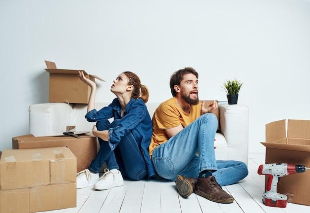 Spostamento uomo felice ristrutturazione e donna sul pavimento in un nuovo appartamento con scatole.