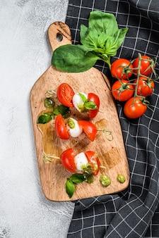 Tartine di mozzarella su spiedini, insalata caprese