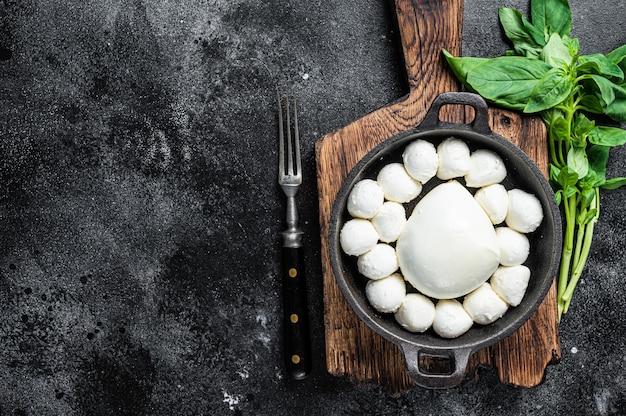 Palline di mozzarella in padella con basilico.