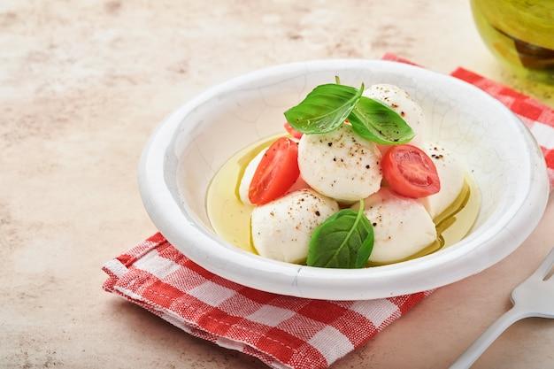 Mozzarella al basilico e pomodorini in piatto di ceramica bianca e pomodorini