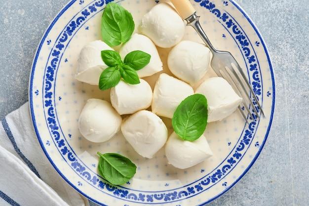 Mozzarella con basilico in piatto di ceramica bianca su fondo di pietra di ardesia