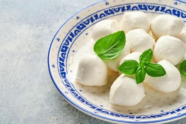 Mozzarella al basilico in piatto di ceramica bianca, pomodoro ciliegino olio d'oliva e macina spezie
