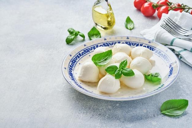 Mozzarella con basilico in piatto di ceramica bianca e ciliegia di pomodoro su fondo di pietra di ardesia