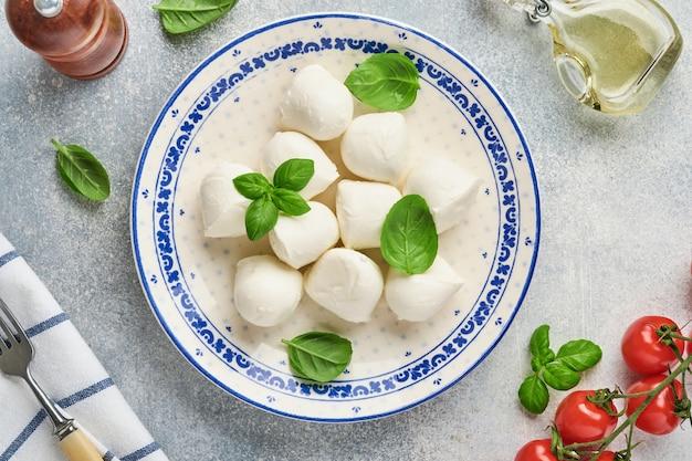 Mozzarella al basilico in piatto di ceramica bianca