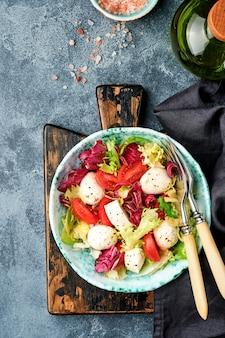Mozzarella, pomodoro e mix di foglie di insalata fresca, superficie scura, vista dall'alto.