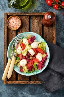 Mozzarella pomodoro e mix di foglie di insalata fresca tavola pietra ardesia