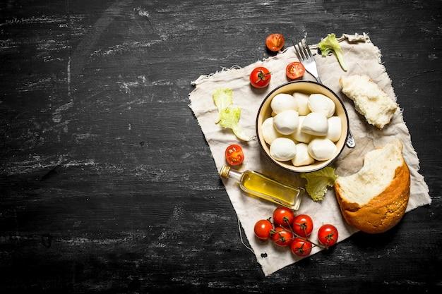 Mozzarella con pane fresco, pomodori e verdure su uno sfondo di legno nero