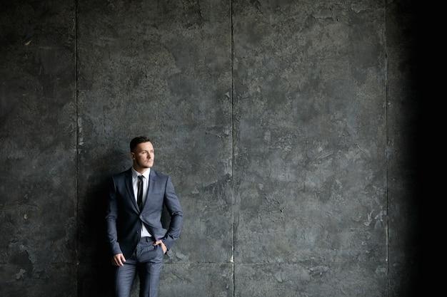 Signor bello. giovane uomo bello in giacca e cravatta in ufficio moderno loft