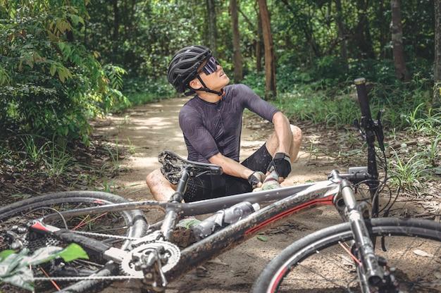 Incidente in mountain bike mtb e pronto soccorso: incidente in bicicletta, infortunio al ginocchio e alla gamba, pronto soccorso per aiutare il motociclista in incidente squadra di pronto soccorso dell'atleta della mountain bike ferita durante l'incidente della corsa.