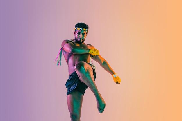 Muay thai. giovane uomo che esercita boxe tailandese su sfondo sfumato alla luce al neon. pratica del combattente, allenamento nelle arti marziali in azione, movimento. stile di vita sano, sport, concetto di cultura asiatica.