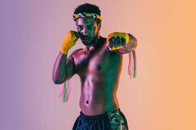 Muay thai giovane uomo che esercita thai boxe sulla parete gradiente