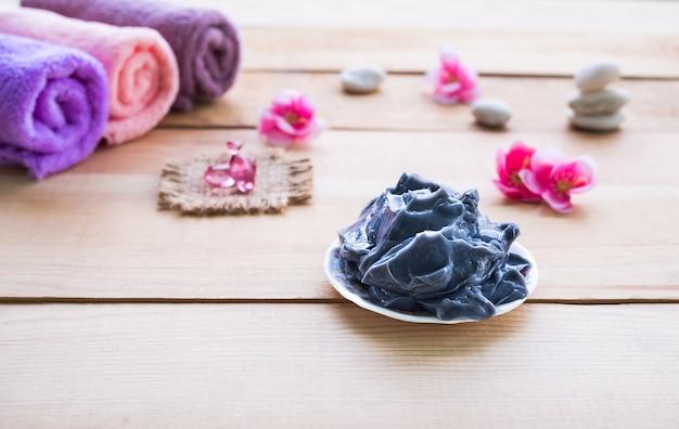 Maschera di fango con vitamina e e asciugamano sul tavolo di legno. per hotel di lusso o massaggi professionali. concetto stabilito della stazione termale di aroma terapia.