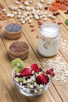 Muesli equilibrato colazione proteica. frutta, semi di bacche, noci. yogurt al cocco. alimento vegetariano di dieta sana. vista dall'alto fondo in legno. copia spazio