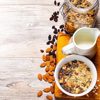 Muesli nella ciotola, vaso e brocca con latte sulla tavola di legno.