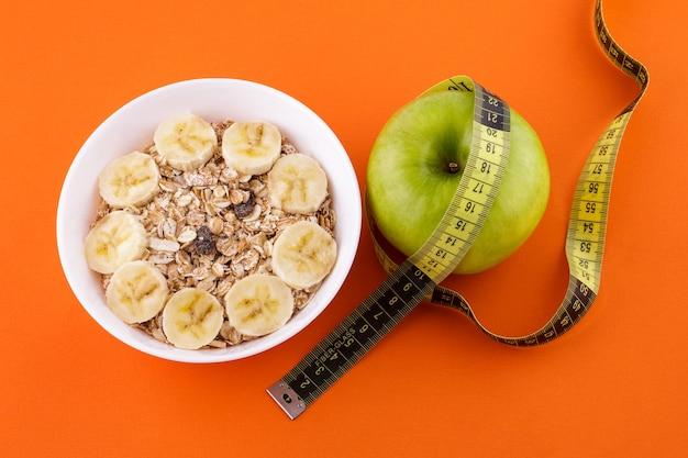 Muesli con banana in un piatto bianco su un'arancia