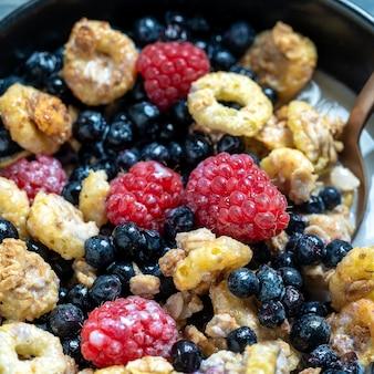 Muesli con lamponi, mirtilli e fiocchi in una ciotola nera, primo piano. cibo sano, concetto di colazione sana