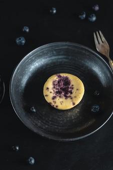Torta di formaggio del muffin con i mirtilli che riempiono sulla zolla scura con la forcella