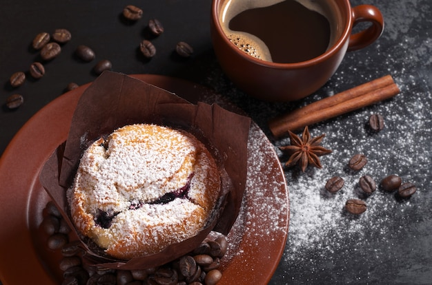 Muffin con mirtilli in piatto marrone e tazza di caffè caldo su sfondo nero