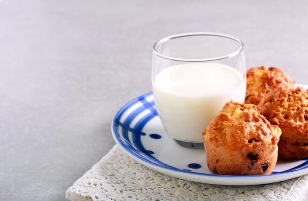 Muffin con mela e uva passa e bicchiere di latte sulla piastra